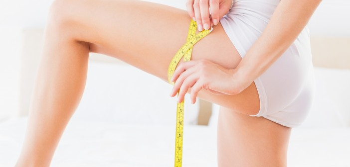 Thin woman measuring her thigh at home in the bedroom