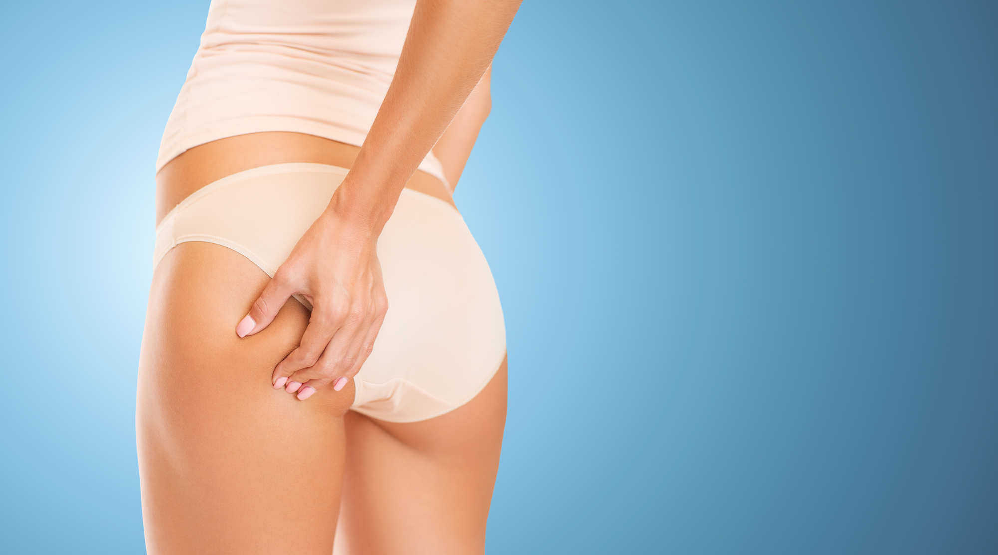 people, health, body care and beauty concept - close up of woman in underwear touching buttock over blue background